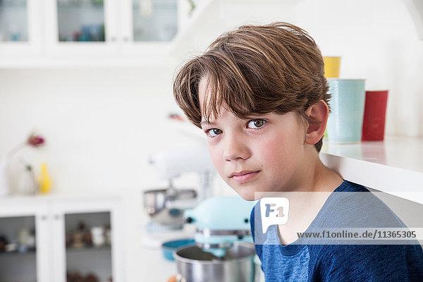 Porträt eines Jungen  der auf einer Küchenarbeitsfläche sitzt