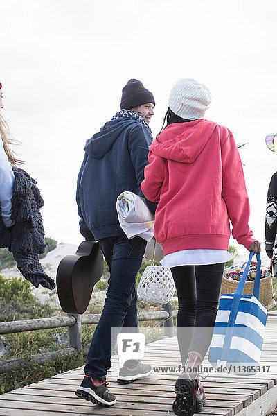 Rückansicht junger erwachsener Picknick-Freunde beim Spaziergang entlang der Strandpromenade am Strand  Western Cape  Südafrika