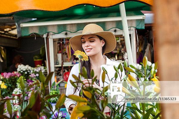 Junge weibliche Touristin riecht Blumen am Marktstand  Split  Dalmatien  Kroatien
