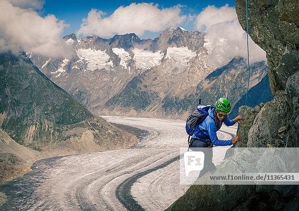 Female climber climbing rock face over Aletsch Glacier  Canton Wallis  Switzerland