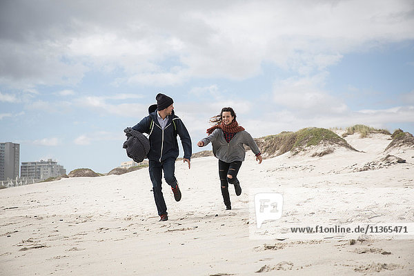 Young couple running on windswept beach  Western Cape  South Africa