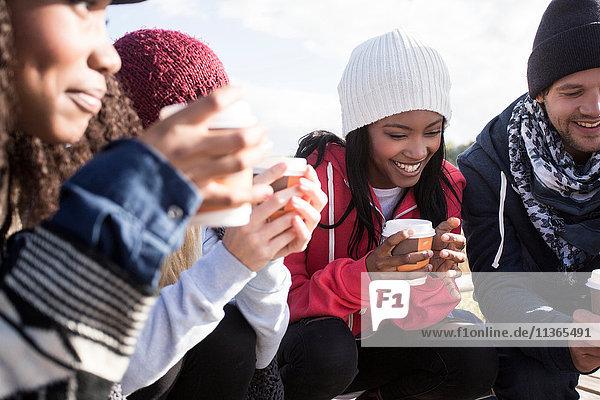 Junge erwachsene Freunde kauern am Strand mit Kaffee zum Mitnehmen  Western Cape  Südafrika