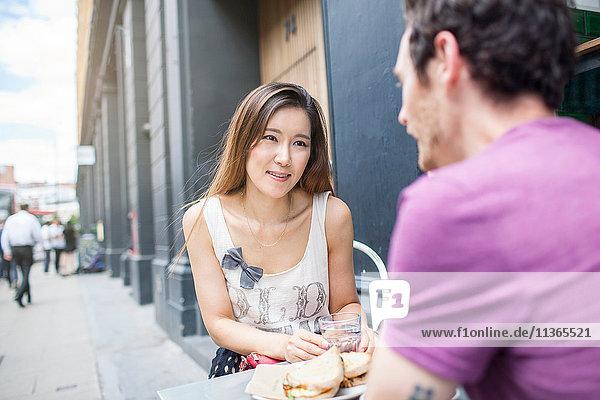 Mittleres erwachsenes Pärchen beim Mittagessen im städtischen Straßencafé