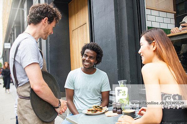Kellner serviert Paar in der Stadt Bürgersteig Cafe