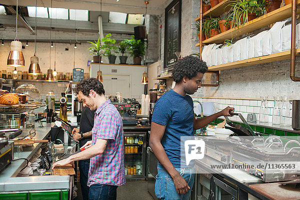 Zwei Kellner bereiten das Essen in der Kaffeeküche zu.