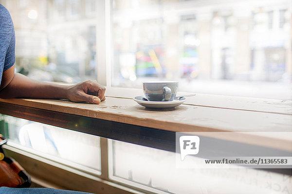 Schnappschuss eines Mannes am Schaufenstersitz eines Cafés