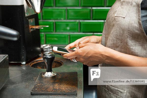Mittelteil eines weiblichen Barista  der in der Café-Küche auf einem Smartphone simst