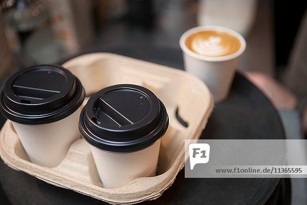 Tablett mit Kaffee in Einwegbechern im Café