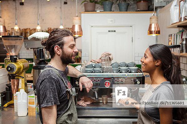 Männliche und weibliche Baristas im Kaffeemaschinengespräch