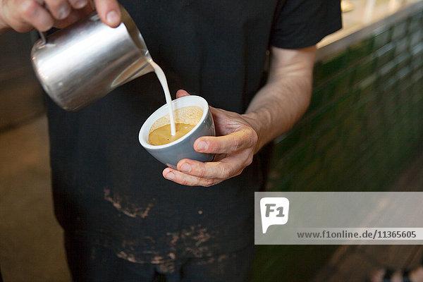 Männliche Barista's Hände gießen Milch in Kaffeetasse im Café