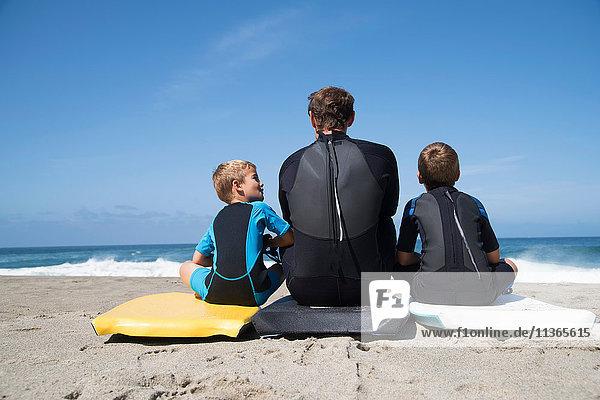 Rückansicht eines Mannes und zweier Söhne auf Bodyboards sitzend  Laguna Beach  Kalifornien  USA