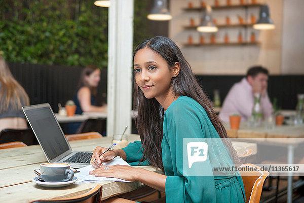Frau blickt beim Papierkram am Kaffeetisch