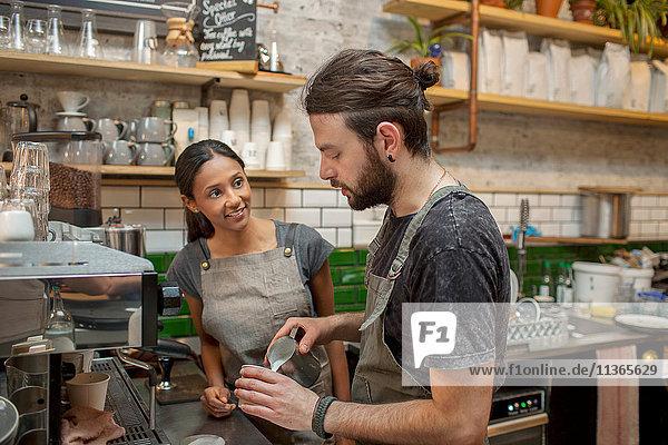 Männliche und weibliche Baristas bei der Kaffeezubereitung im Cafe