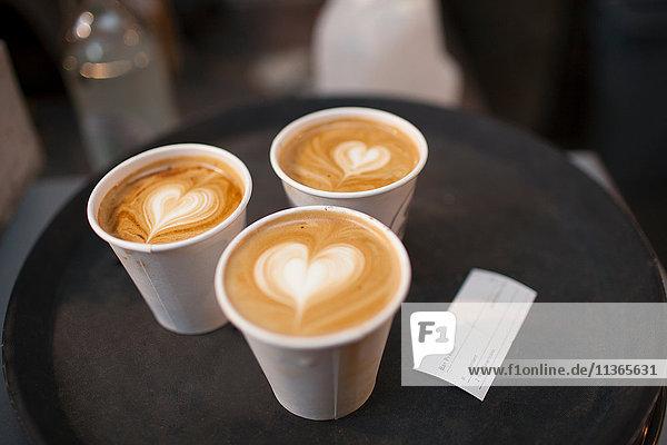 Drei Tassen Kaffee zum Mitnehmen mit herzförmigen Spitzen
