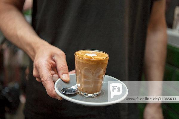 Ein Schuss Barista mit einem Glas Kaffee im Cafe.