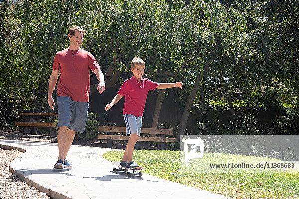 Junge mit Vater übt im Park auf dem Skateboard