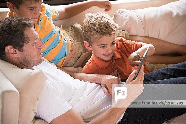 Mann und zwei Söhne zeigen auf digitales Tablett auf dem Sofa