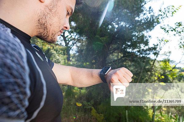 Männlicher Läufer kontrolliert Smartwatch im Park  Split  Dalmatien  Kroatien