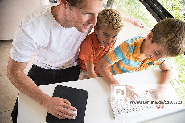 Mann und zwei Söhne beim Tippen auf der Desktop-Computertastatur