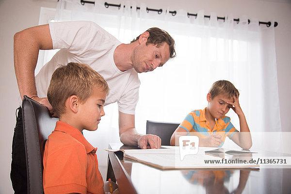 Mann berät zwei Söhne bei den Hausaufgaben am Tisch