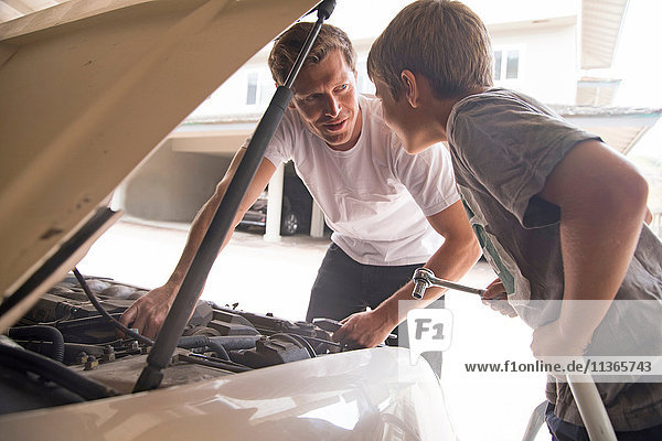 Father explaining car maintenance to son under car hood
