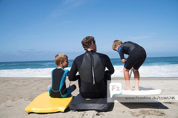 Rückansicht von Vater und zwei Söhnen beim Üben mit Bodyboards am Strand  Laguna Beach  Kalifornien  USA
