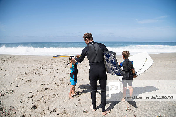 Rear view of father and two sons preparing to go bodyboarding on beach  Laguna Beach  California  USA
