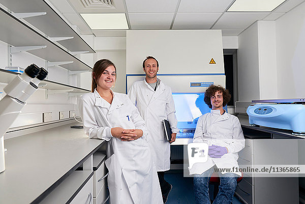 Scientists in laboratory looking at camera smiling