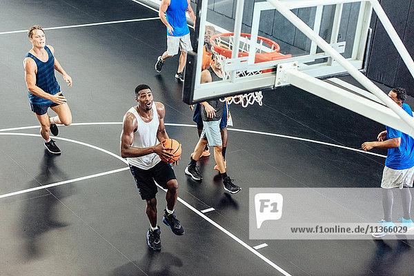 Male basketball team throwing ball into hoop on basketball court