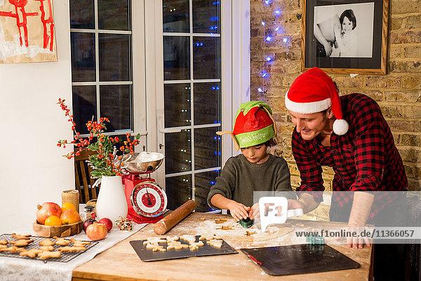Mann und Sohn bereiten an der Küchentheke Weihnachtsplätzchen zu