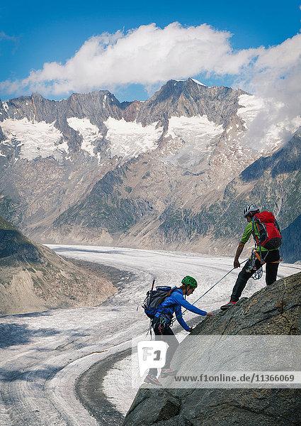 Couple climbing up ridge over Aletsch Glacier  Canton Wallis  Switzerland