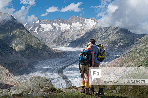 Hiking couple looking out over Aletsch Glacier  Canton Wallis  Switzerland