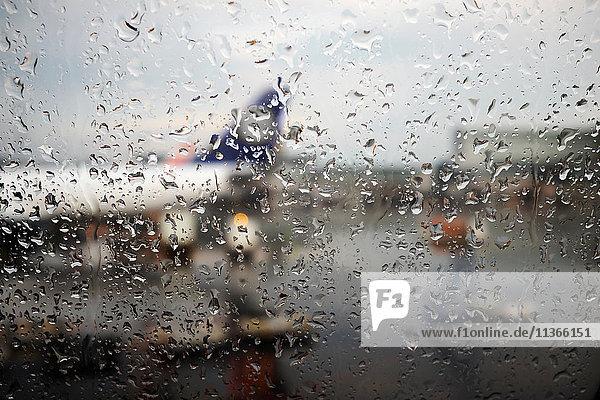 Fensteransicht eines im Regen auf dem Flughafen-Vorfeld geparkten Flugzeugs Fensteransicht eines im Regen auf dem Flughafen-Vorfeld geparkten Flugzeugs