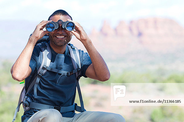 Portrait of young man looking through binoculars  Sedona  Arizona  USA