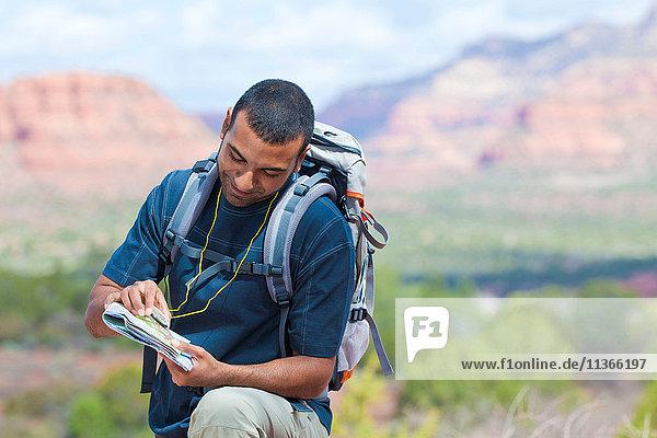 Young male hiker looking at map  Sedona  Arizona  USA
