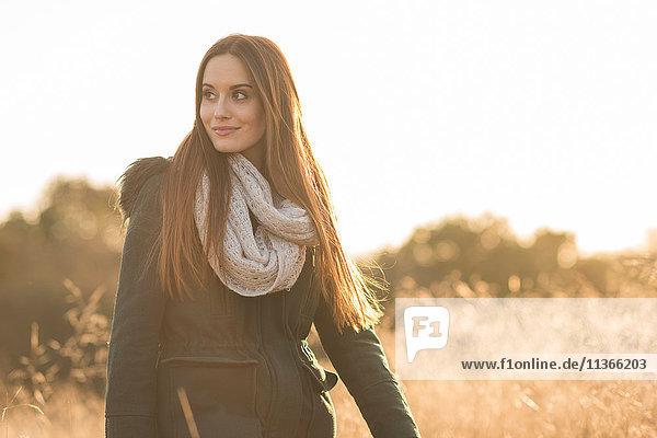Porträt einer jungen Frau beim Gang durchs Feld