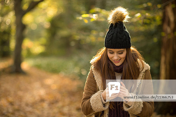Young woman in forest  looking at smartphone  smiling