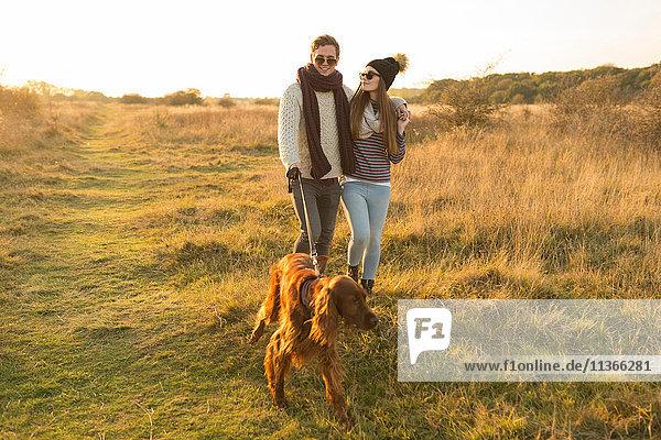 Junges Paar beim Hundeausführen im Feld