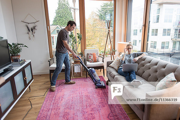 Mid Erwachsene Mann Staubsaugen mit Freundin auf dem Sofa liegend mit Laptop
