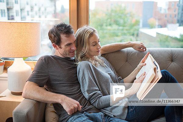 Mittleres erwachsenes Paar  das auf dem Sofa liegt und ein Buch liest.