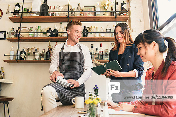 Waiter and female customers discussing menu in restaurant