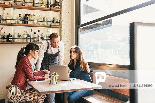 Kellner und weibliche Kunden schauen im Restaurant auf den Laptop