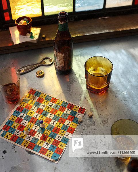 Bierflasche und Gläser mit Brettspiel auf Kneipentisch