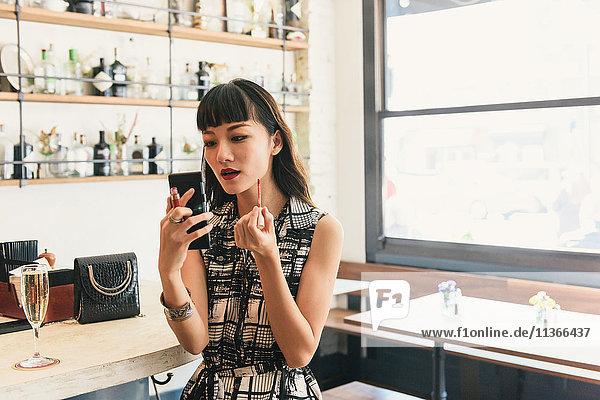 Junge Frau trägt Lippenstift in der Cocktailbar auf