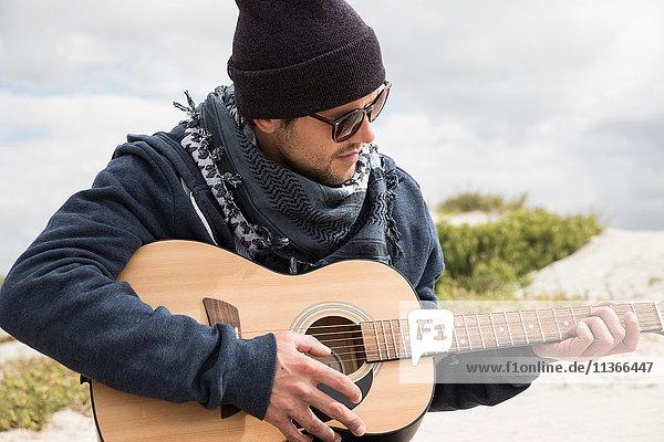 Junger Mann spielt akustische Gitarre am Strand  Western Cape  Südafrika