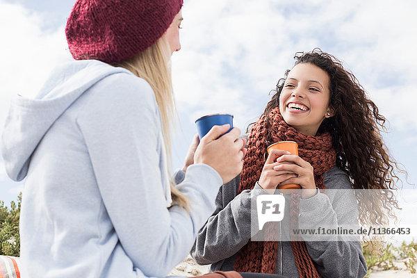 Zwei junge Frauen lachen beim Strandpicknick  Western Cape  Südafrika