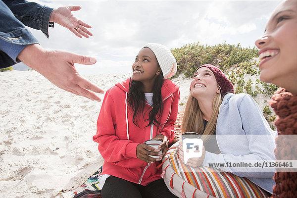 Junge Frauen und Männer picknicken am Strand  Western Cape  Südafrika