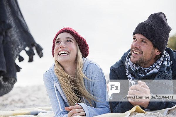 Junges Paar schaut von einer Picknickdecke am Strand auf  Western Cape  Südafrika