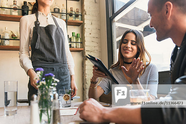 Junge Frau bezahlt Rechnung am Cocktail-Bar-Tisch