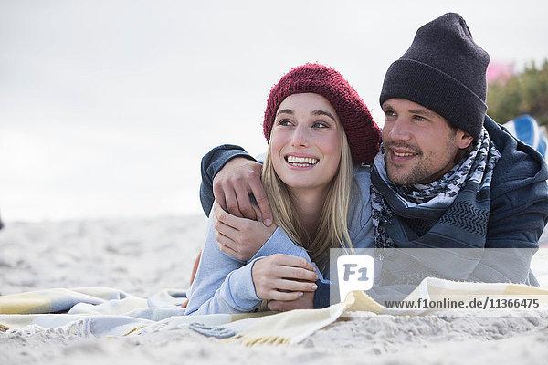 Romantisches junges Paar liegt auf einer Picknickdecke am Strand  Western Cape  Südafrika